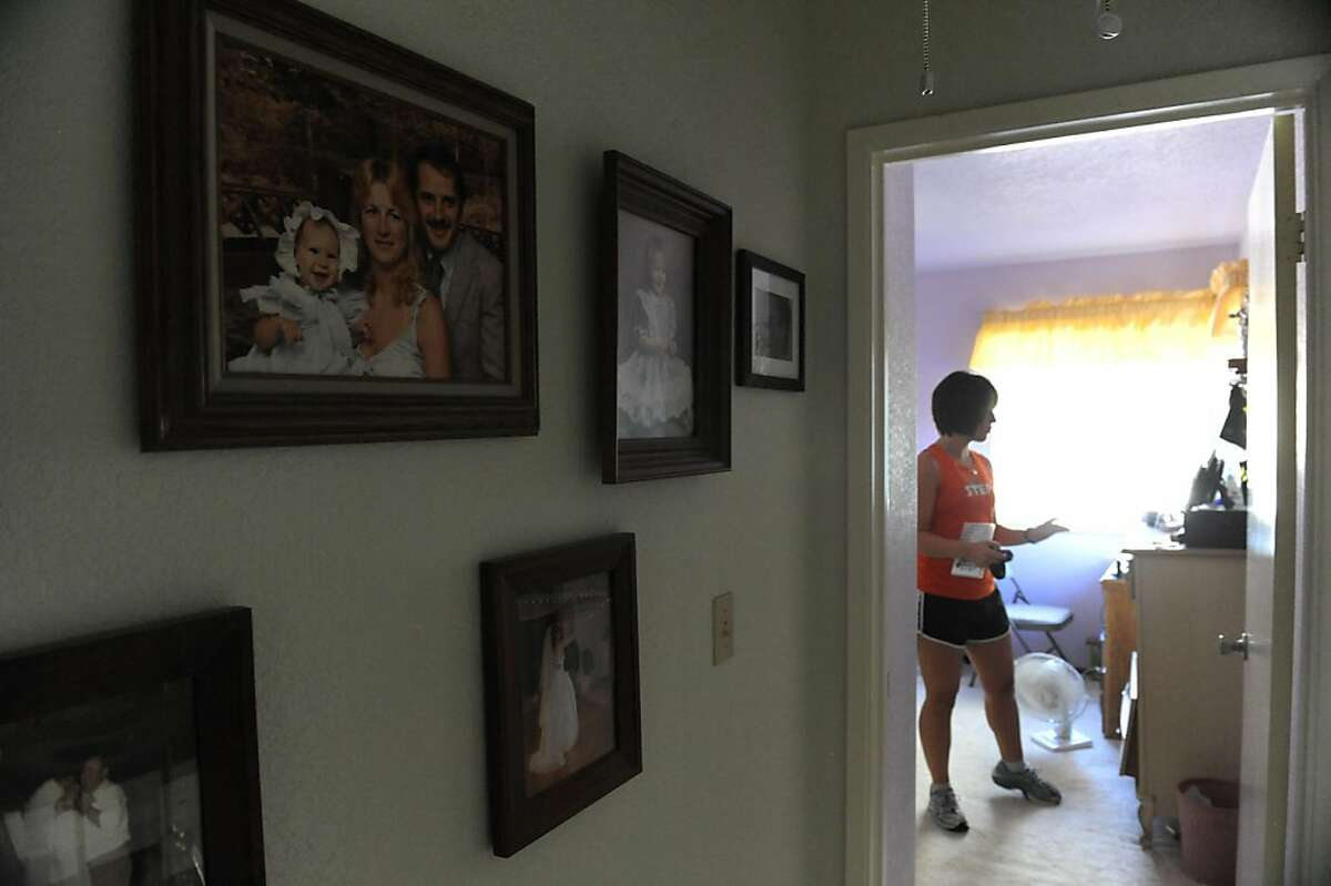 Mandy Durkin prepares to go to work in Fairfield on October 14, 2011. Family photos are seen on the wall of her childhood home where Durkin has temporarily moved back to with her parents.