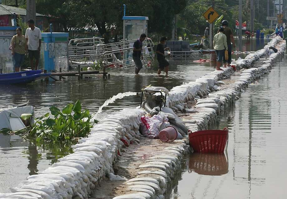 Residents walk on sandbag barriers set up on a street to prevent from flooding in Pathumthani province, central Thailand, Wednesday, Oct. 12, 2011. Thailand's worst floods in half a century swamp more than two-thirds of country and inflict billions of dollars in damage in what has become a slow-motion catastrophe fueled by relentless monsoon rains. (AP Photo/Apichart Weerawong) Photo: Apichart Weerawong, AP