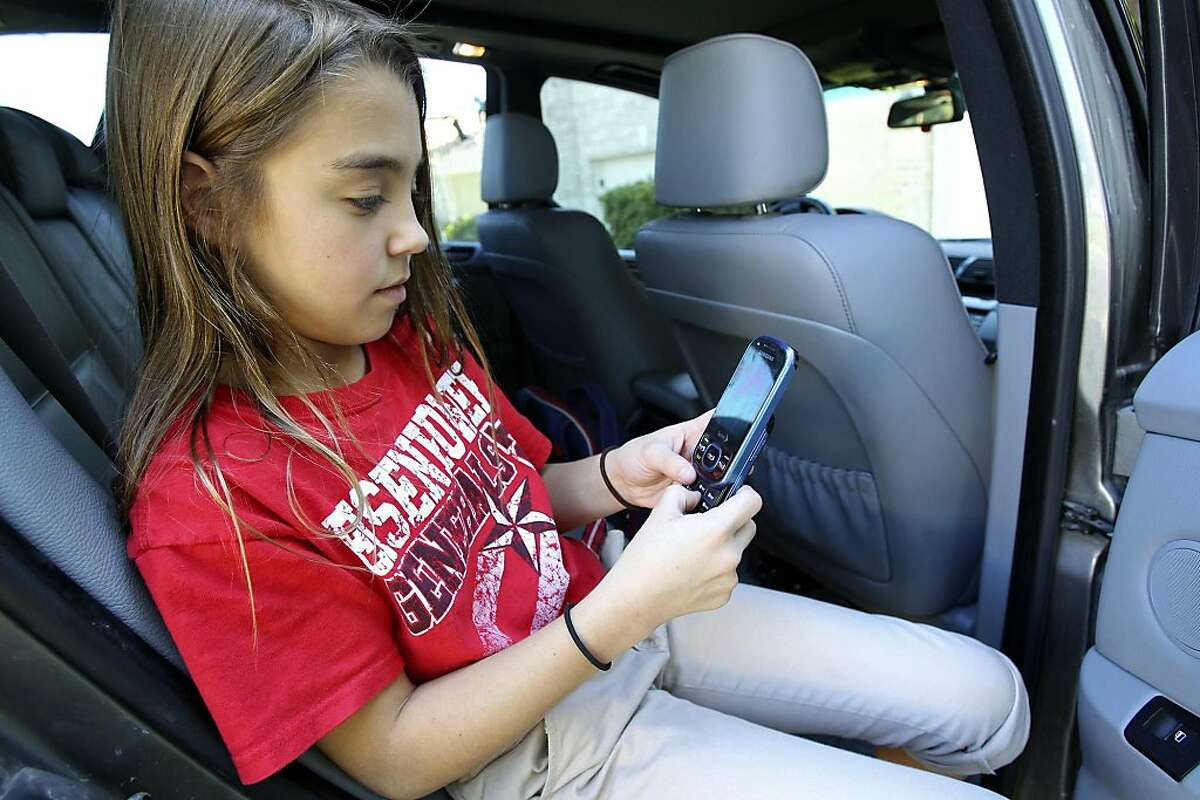Eleven-year-old Devyn (CQ) Darmstetter (CQ) uses her phone while waiting in her ther's car on October 13, 2011. Tom Reel/Staff