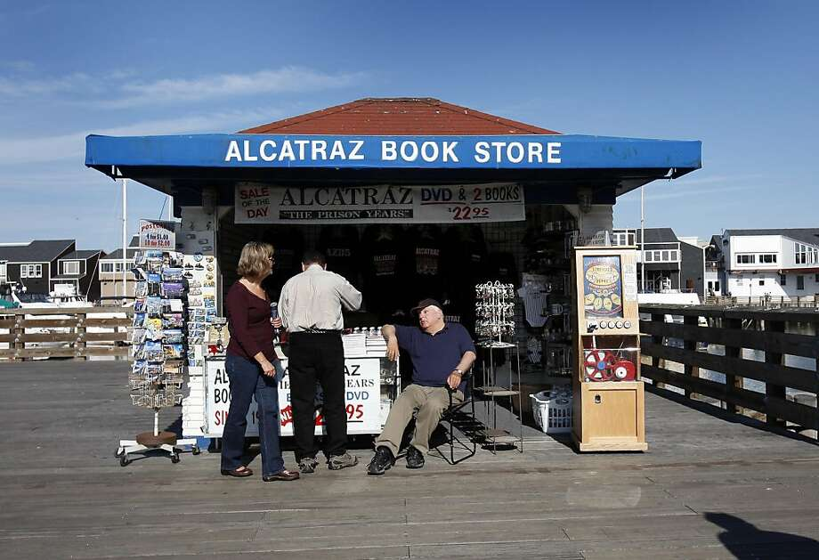 Peter Dracopoulous (right) talks with some tourists from his souvenir shop. Peter Dracopoulous runs a tiny souvenir stand near Pier 41 in San Francisco, Calif.  He is blind and in danger of losing his home after taking out money to support his stand. Photo: Brant Ward, The Chronicle