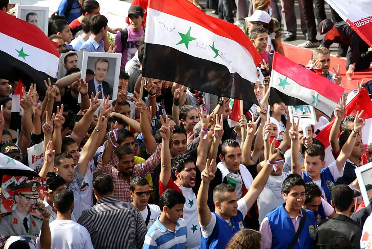 Supporters of Syrian President Bashar al-Assad wave Syrian flags while holding a picture of his father, late president Hafez al-Assad, during a pro-regime rally in Damascus on October 12, 2011. Assad's regime is facing international pressure amid a violent crackdown on anti-government protests that broke out in March across Syria. AFP PHOTO/LOUAI BESHARA (Photo credit should read LOUAI BESHARA/AFP/Getty Images)