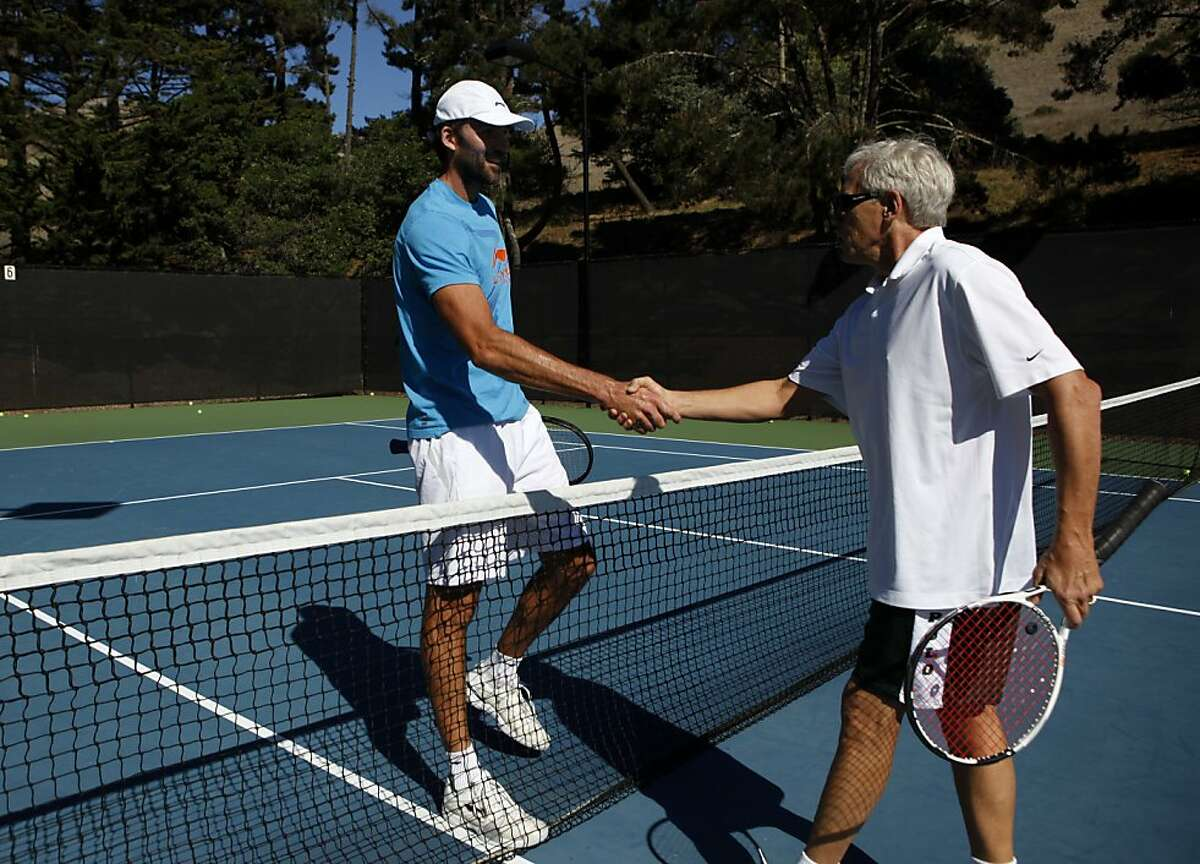 San Francisco Chronicle columnist Scott Ostler, right, shakes hands with professional tennis player Ivo Karlovic after Ostler took some serves on Thursday, October 13, 2011 at the Tiburon Peninsula Club in Tiburon, Calif. Ivo Karlovic serve is able to reach speeds of 150 miles per hour.