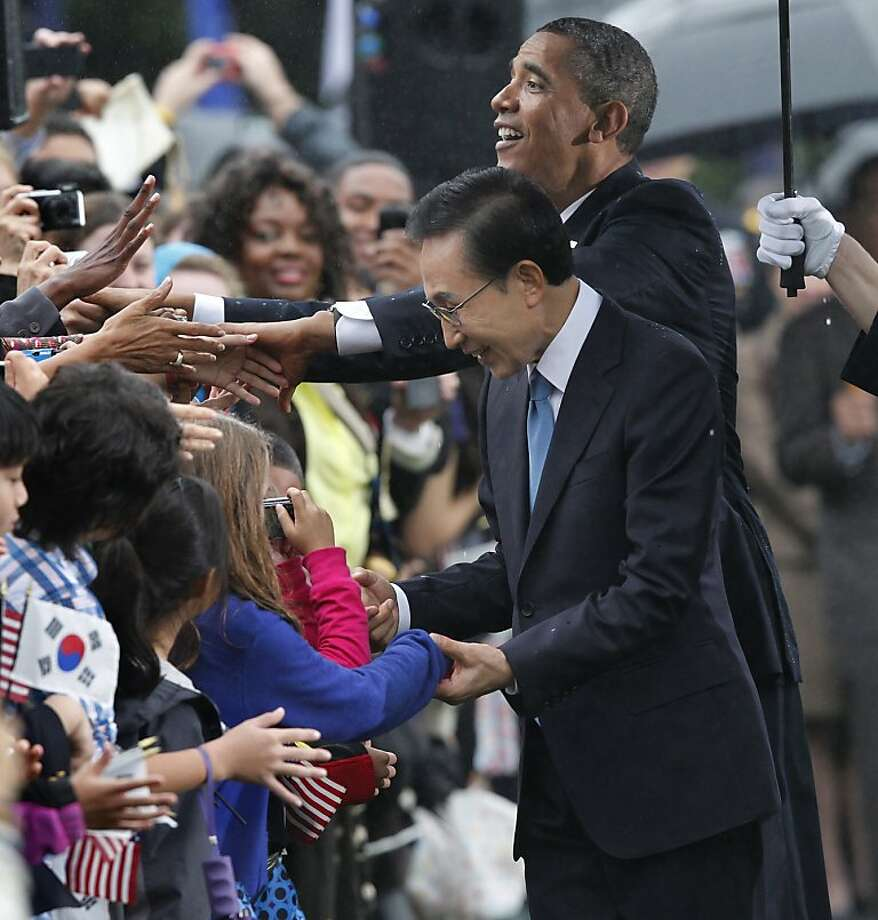 President Barack Obama and South Korean President Lee Myung-bak are welcomed by local school children during a rainy state arrival ceremony,  Thursday, Oct. 13, 2011, on the South Lawn of the White House in Washington.  (AP Photo/J. Scott Applewhite) Photo: J. Scott Applewhite, AP
