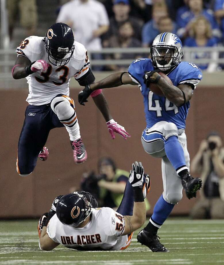 Detroit Lions running back Jahvid Best (44) runs for a 43-yard gain after eluding Chicago Bears linebacker Brian Urlacher, on the ground, and cornerback Charles Tillman (33) in the fourth quarter of NFL football game in Detroit, Monday, Oct. 10, 2011. (AP Photo/Paul Sancya) Photo: Paul Sancya, AP