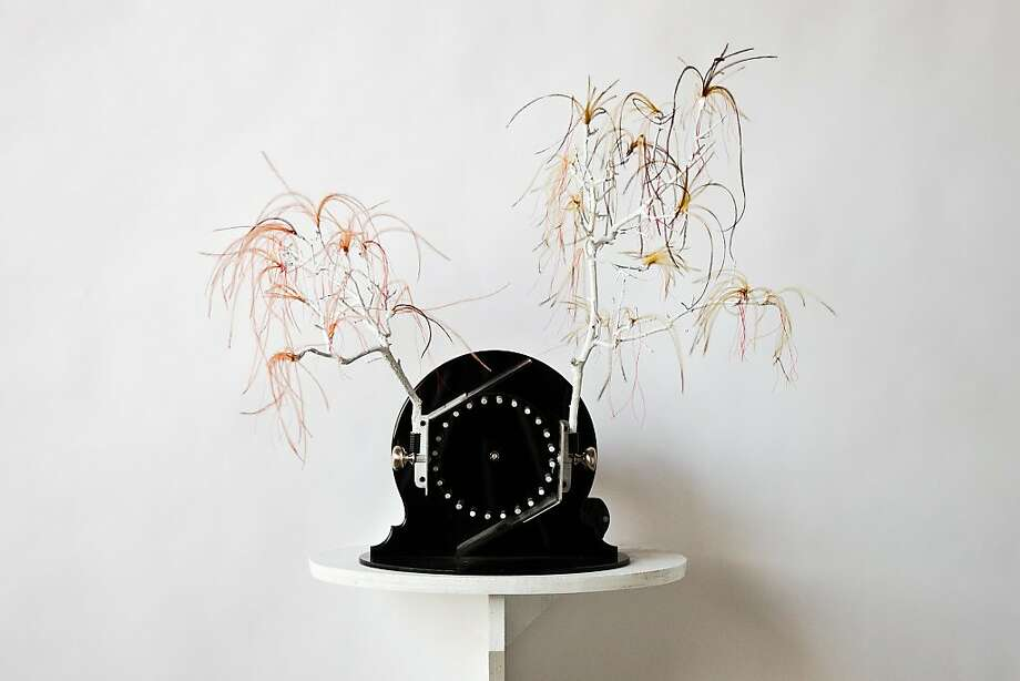 "Anja Ulfeldt's ""Everything You Touch,"" white branches, crowned with wispy, yellow and scarlet feathers, top an ebony base with attached doorknobs and other hardware. Photo: Courtesy Of The Artist"