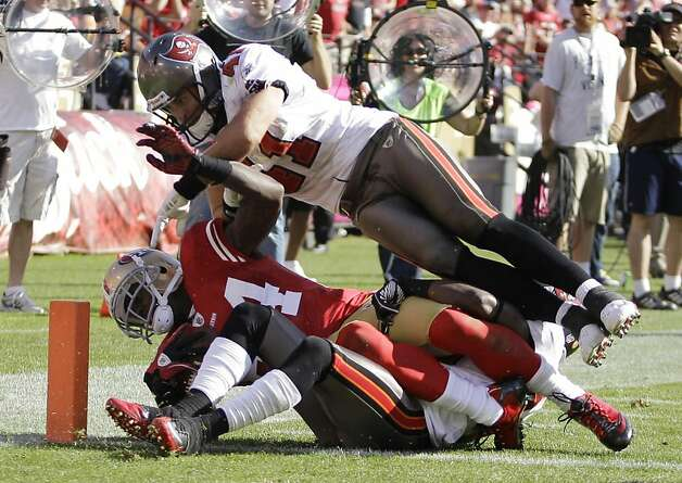 San Francisco 49ers wide receiver Josh Morgan is injured on this play as Tampa Bay Buccaneers safety Corey Lynch falls on top of him during the fourth quarter of their NFL football game in San Francisco, Sunday, Oct. 9, 2011. San Francisco won the game 48-3. Morgan finished with five catches for 75 yards. (AP Photo/Ben Margot) Ran on: 10-11-2011 Corey Lynch falls on Joshua Morgan on the play on which Morgan's leg was broken. Photo: Ben Margot, AP