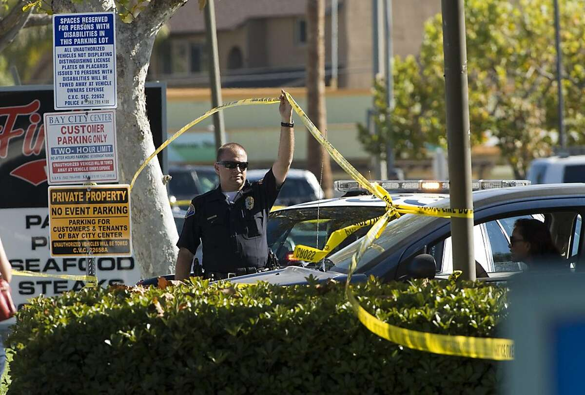 An offer allows a vehicle to leave the perimeter near the site where six people were killed and three were wounded in a shooting at a hair salon in Seal Beach, Calif., Wednesday, Oct. 12, 2011. The six deaths were confirmed and the other three victims were taken to a hospital in critical condition, police Sgt. Steve Bowles told The Associated Press. (AP Photo/Orange County Register, Jebb Harris) MAGS OUT; LOS ANGELES TIMES OUT