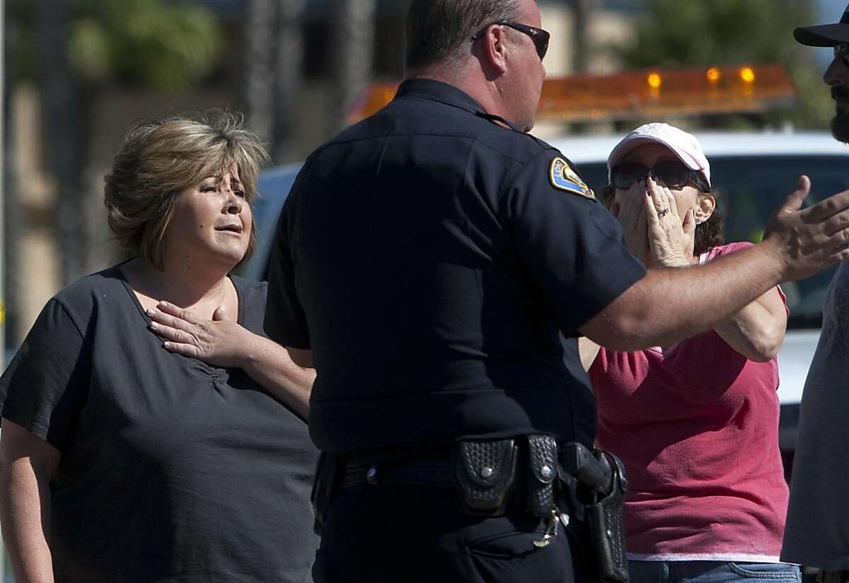 Onlookers react near the site where six people were killed and three were wounded in a shooting at a hair salon in Seal Beach, Calif., Wednesday, Oct. 12, 2011. Police Sgt. Steve Bowles says a man was taken into custody near the scene and investigators are trying to determine if he has a relationship to the salon or anyone there. (AP Photo/Los Angeles Times, Gina Ferazzi) NO FORNS; NO SALES; MAGS OUT; ORANGE COUNTY REGISTER OUT; LOS ANGELES DAILY NEWS OUT; VENTURA COUNTY STAR OUT; INLAND VALLEY DAILY BULLETIN OUT; SAN BERNARDINO SUN OUT; MANDATORY CREDIT, TV OUT