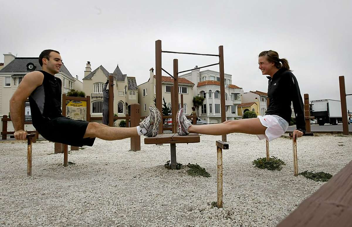 Aaron Beyer and Whitney Howe, of San Francisco, work out at the Marina Green on Wednesday August 19, 2009 in San Francisco, Calif., before a morning run, as folks are getting mixed messages about exercise these days, some say 20 minutes a day other an hour to really make a difference. Ran on: 08-27-2009 Aaron Beyer and Whitney Howe of San Francisco warm up at the Marina Green before their morning run.