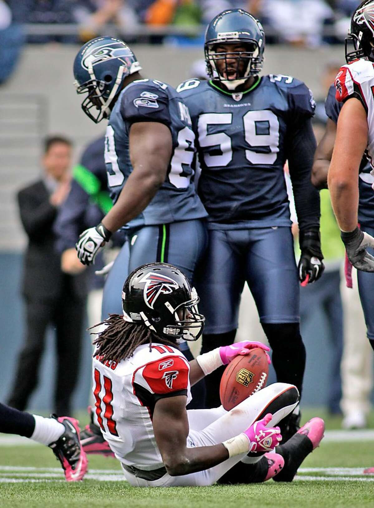 Seattle Seahawks Aaron Curry (59) watch Atlanta Falcons Julio Jones after Jones was tackled in the second half of a NFL football game, Sunday, Oct. 2, 2011, in Seattle. (AP Photo/Ted S. Warren)