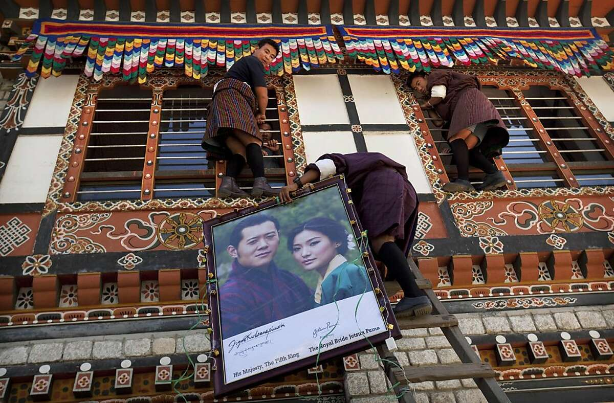Bhutanese staff and students prepare to place a portrait of King Jigme Khesar Namgyal Wangchuck and future Queen Jetsun Pema, outside the Lungten Zanpa School, their alma mater, in the capital of Thimphu, Bhutan, Wednesday, Oct. 12, 2011. The 31-year-old reformist monarch of the small Himalayan Kingdom will wed his commoner bride in a series ceremonies set for Thursday. (AP Photo/Kevin Frayer)