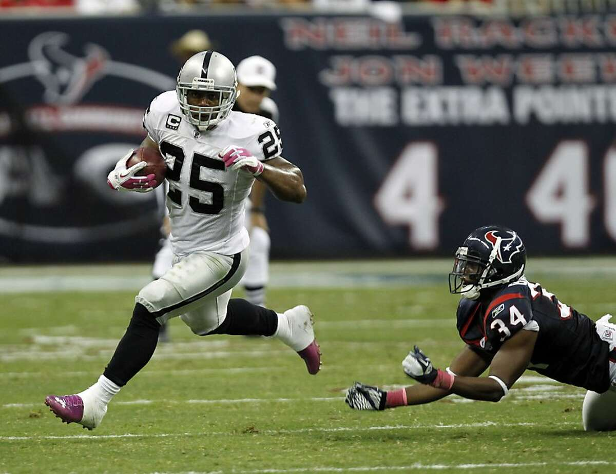 Oakland Raiders running back Rock Cartwright (25) and Houston Texans' Dominique Barber (34) in the fourth quarter of an NFL football game Sunday, Oct. 9, 2011, in Houston. (AP Photo/Gerald Herbert)