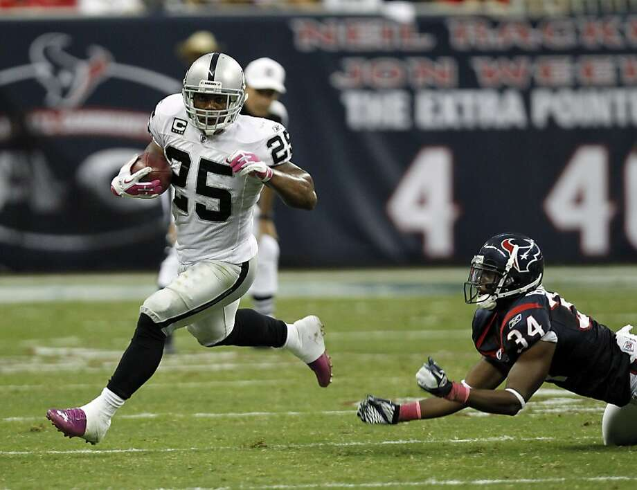 Oakland Raiders running back Rock Cartwright (25) and Houston Texans' Dominique Barber (34) in the fourth quarter of an NFL football game Sunday, Oct. 9, 2011, in Houston. (AP Photo/Gerald Herbert) Photo: Gerald Herbert, AP