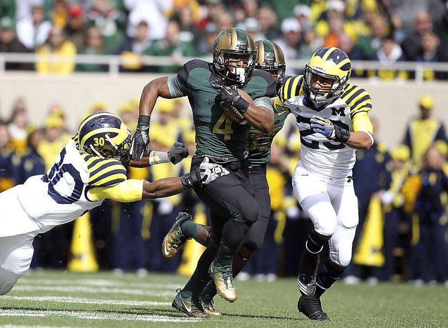 EAST LANSING, MI - OCTOBER 15: Edwin Baker #4 of the Michigan State Spartans runs for a first down in the second quarter as Thomas Gordon #30 and Troy Woolfolk #29 attempt to make the stop during the game at Spartan Stadium on October 15, 2011 in East Lansing, Michigan. Michigan State defeated Michigan 28-14.  (Photo by Leon Halip/Getty Images) Photo: Leon Halip, Getty Images