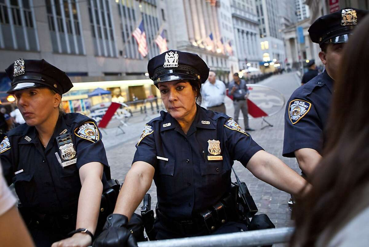 """New York City police officers monitor protesters affiliated with the """"Occupy Wall Street"""" protests as they march near the New York Stock Exchange in New York, Monday, Oct. 10, 2011. The march started and finished in Zuccotti Park. (AP Photo/Andrew Burton)"""