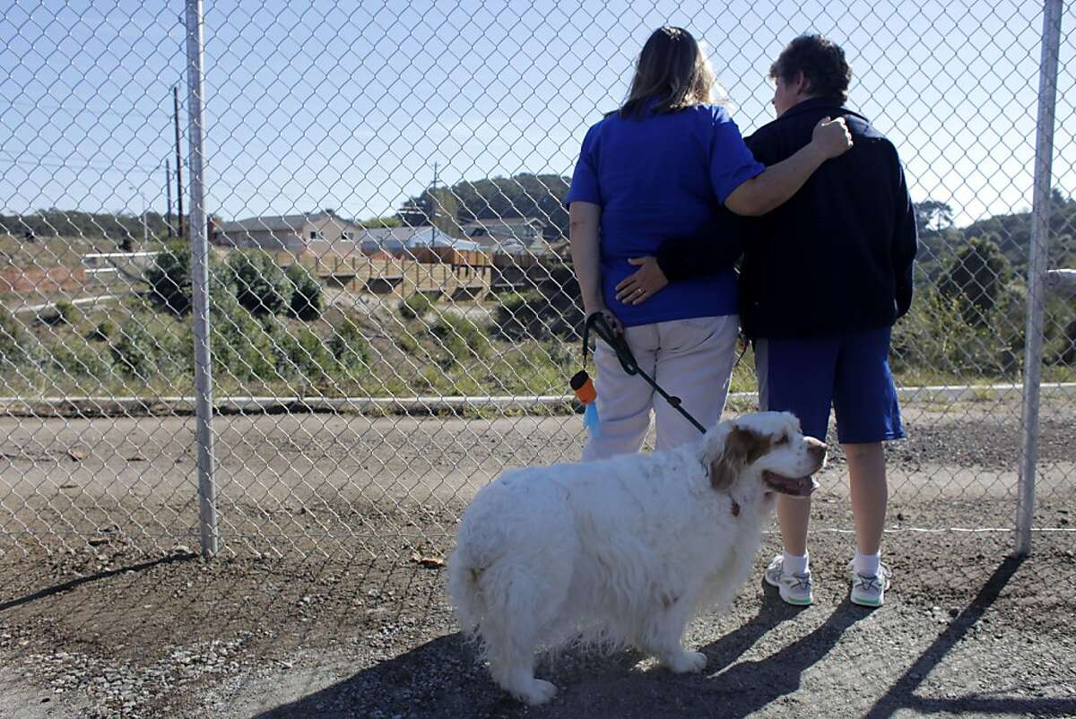 """Marla Shelmadine stands with her partner Nancy Wynschenk and their dog """"Lizzie"""" as they remember their neighbors who lost their lives after the Glenview Drive opens, Wednesday October 12, 2011, in San Bruno, Calif. After 13 months since the PG&E explosion residents with the Mayor and other officials remove the barricade blocking Glenview."""