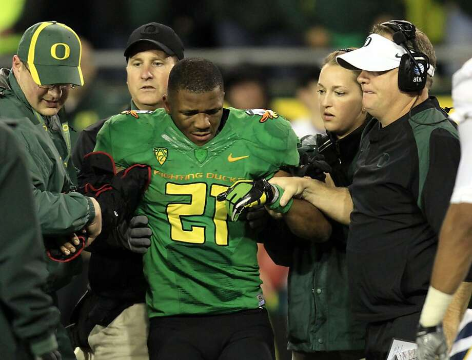 Oregon head football coach Chip Kelly, right, and others help LaMichael James off the field after he injured his right arm during the second half of their NCAA football game against California in Eugene, Ore.,  Thursday, Oct. 6, 2011. James ran for 239 yards and a touchdown before he was carted off the field as Oregon beat California 43-15.(AP Photo/Don Ryan) Photo: Don Ryan, AP