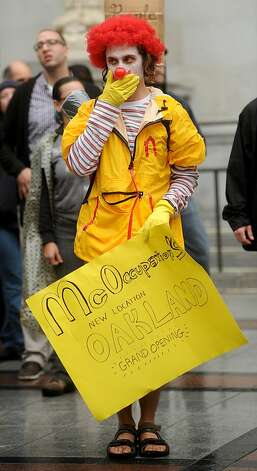 A protester dressed as Ronald McDonald who gave his name as Pipes, celebrates the spread of the Occupy protest movement to Oakland, Calif., on Monday, Oct. 10, 2011. Photo: Noah Berger, Special To The Chronicle