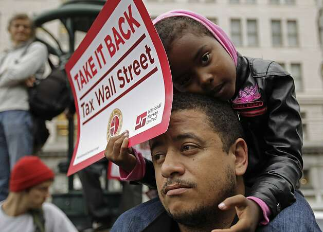 Kamayah Riley, 5, rests atop her father Manuel Riley's shoulders as he they participate in an Occupy Oakland rally Monday, Oct. 10, 2011, in Oakland, Calif.  Protestors came to rally against the influence of corporate money in politics among a host of other issues, and in sympathy with the Occupy Wall Street protest. (AP Photo/Ben Margot) Photo: Ben Margot, AP