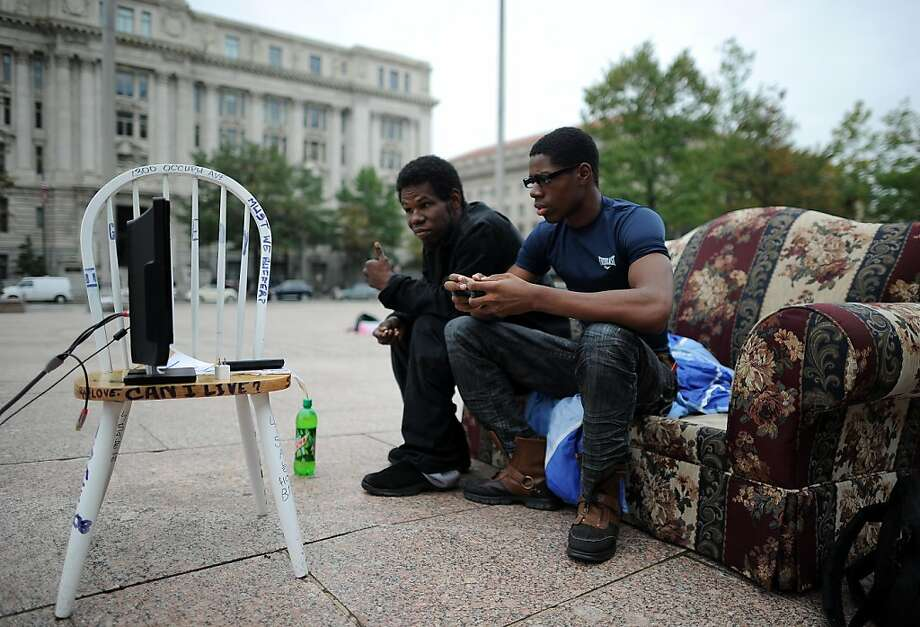 Two protesters play video games during anti-corporations demonstration at the Freedom Plaza in Washington, DC, on October 11, 2011. Police arrested six protesters Tuesday who surged into a Senate office building in Washington, chanting slogans for about 15 minutes before officers intervened. Stop the Machine has been occupying Freedom Plaza near the White House since Thursday. A second, younger group called Occupy DC, an offshoot of Occupy Wall Street, has been in downtown McPherson Square since October 1. AFP Photo/Jewel Samad (Photo credit should read JEWEL SAMAD/AFP/Getty Images) Photo: Jewel Samad, AFP/Getty Images