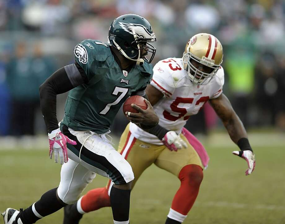 Philadelphia Eagles quarterback Michael Vick (7) scrambles as he pursued by San Francisco 49ers inside linebacker NaVorro Bowman (53) in the second half of an NFL football game Sunday, Oct. 2, 2011 in Philadelphia. (AP Photo/Michael Perez) Photo: Michael Perez, AP