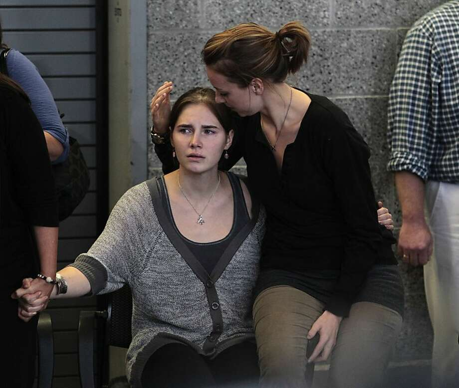 Amanda Knox, left, is comforted by her sister, Deanna Knox, during a news conference shortly after her arrival at Seattle-Tacoma International Airport Tuesday, Oct. 4, 2011, in Seattle. It's been four years since the University of Washington student left for the study abroad program in Perugia and landed in prison. The group Friends of Amanda Knox and others have been awaiting her return since an Italian appeals court on Monday overturned her conviction of sexually assaulting and killing her British roommate, Meredith Kercher. (AP Photo/Elaine Thompson) Photo: Elaine Thompson, AP