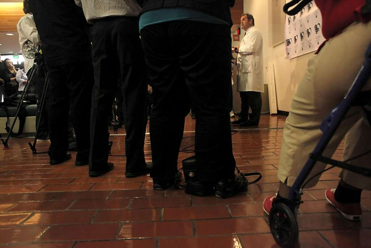 Patients and media listen stop to listen to Dr. Geoff Manley, Chief of Neurosurgery, announce that patient Bryan Stow is being transferred to a undisclosed rehabilitation facility, Tuesday Oct. 10, 2011, at San Francisco General Hospital and Trauma Center in San Francisco, Calif.