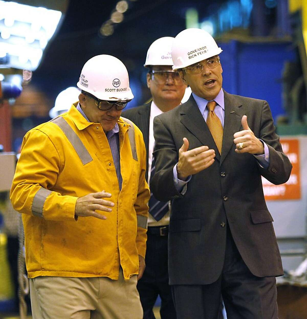 Republican presidential candidate, Texas Gov. Rick Perry, right, talks with Scott Buckiso as he tours the United States Steel Irvin Works in West Mifflin, Pa., Frida, Oct. 14, 2011, before he spoke about energy and environmental regulations. (AP Photo/Keith Srakocic)
