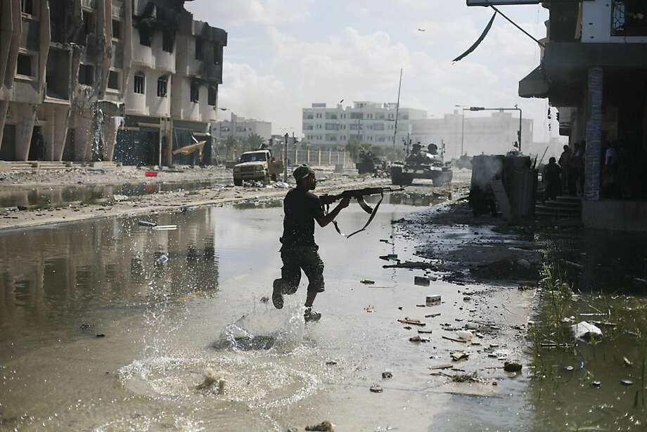 A Libyan revolutionary fighter fires with his machine gun while attacking pro-Gadhafi forces in downtown Sirte, Libya, Friday, Oct. 14, 2011. Revolutionary forces pounded Moammar Gadhafi's supporters holed up in two neighborhoods with rocket and machine-gun fire Friday in Sirte, but the loyalists showed no sign of giving up in the fugitive leader's hometown. (AP Photo/Manu Brabo) Photo: Manu Brabo, AP