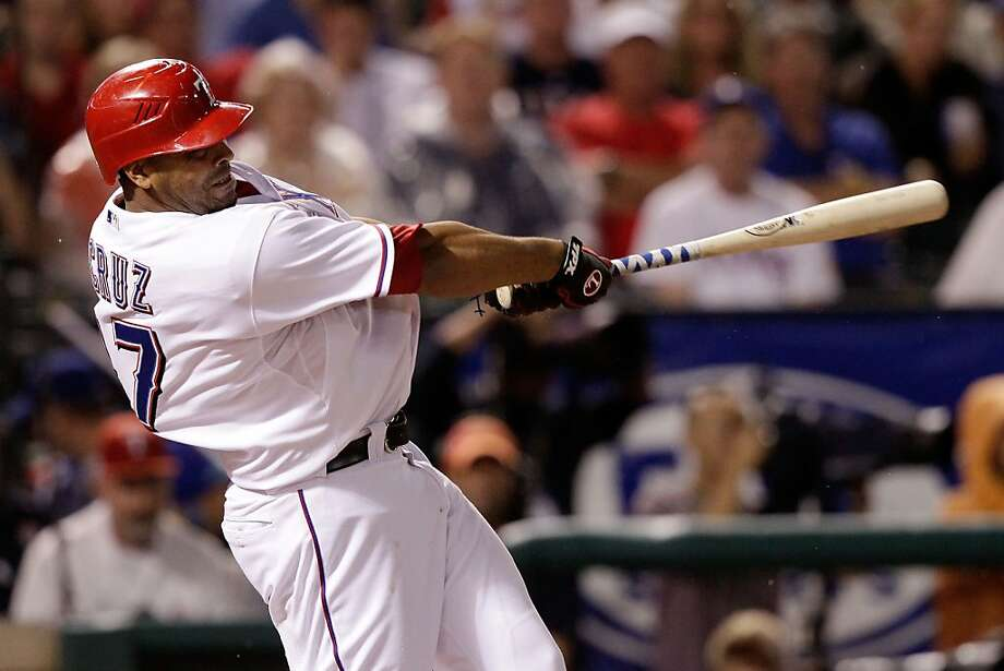 ARLINGTON, TX - OCTOBER 08:  Nelson Cruz #17 of the Texas Rangers hits a solo home run in the fourth inning of Game One of the American League Championship Series against the Detroit Tigers at Rangers Ballpark in Arlington on October 8, 2011 in Arlington, Texas.  (Photo by Bob Levey/Getty Images) Photo: Bob Levey, Getty Images