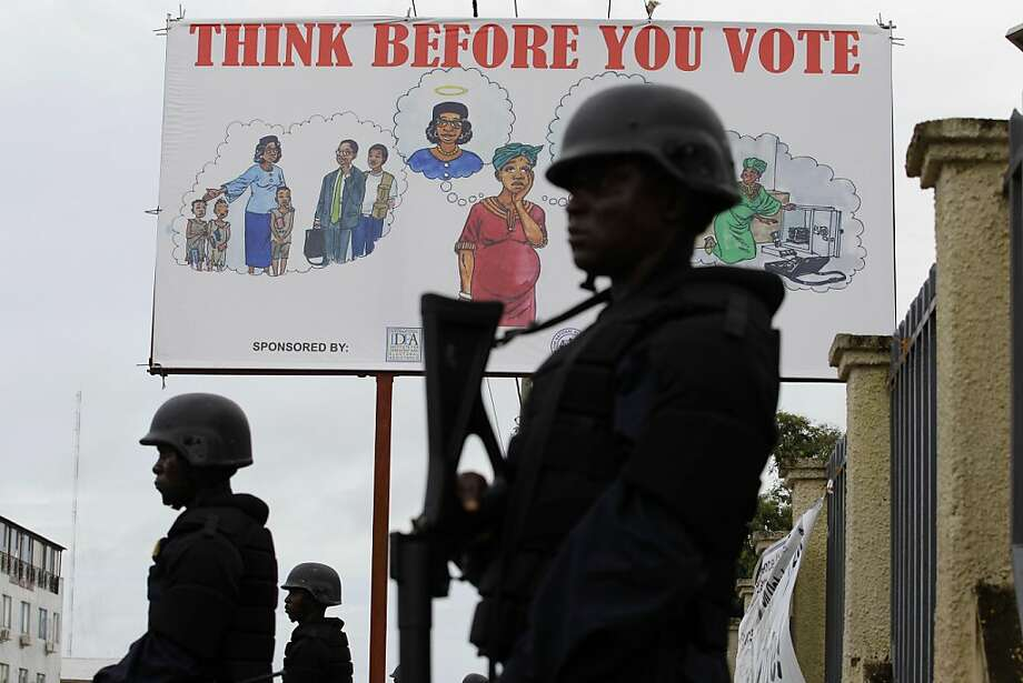 Liberian police equipped with riot gear stand guard outside the headquarters of the National Elections Commission as the NEC prepared to announce the first partial presidential election results, in Monrovia, Liberia Thursday, Oct. 13, 2011. Preliminary partial results from Liberia's presidential election show Nobel Peace Prize winner Ellen Johnson Sirleaf failing to reach the majority needed to avoid a runoff.(AP Photo/Rebecca Blackwell) Photo: Rebecca Blackwell, AP