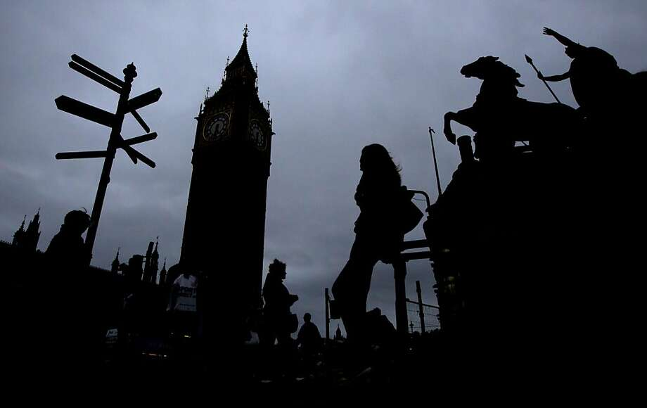 A woman is silhouetted next to the Big Ben clock tower in London, Monday, Oct. 10, 2011.  Big Ben has a little bend.  Experts say the world-famous neogothic clock tower is listing gently, and documents recently published by Britain's Parliament show that the top of its gilded spire is about one-and-a-half feet (nearly half a meter) out of line.  The tower - colloquially known as Big Ben after its massive bell - has been slightly off center since it was erected in the 19th century. Like many old buildings its position has been shifting imperceptibly for years as the ground beneath it subsides.  (AP Photo/Matt Dunham) Photo: Matt Dunham, AP