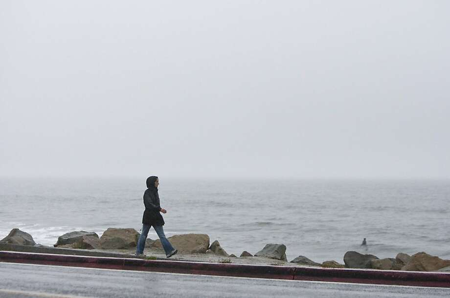 A pedestrian walks along Highway 1 during a rainstorm in Half Moon Bay, Calif., on Monday, October 10, 2011. Photo: Laura Morton, Special To The Chronicle
