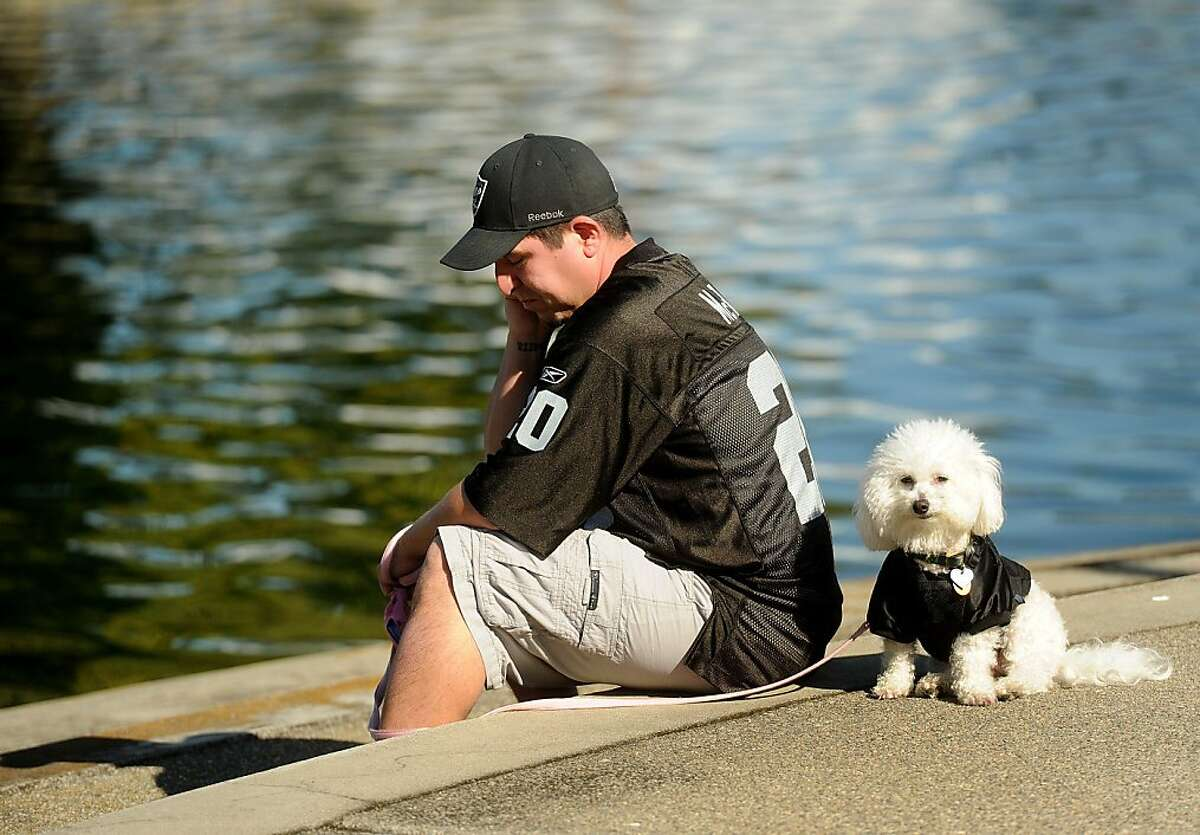 Raiders fans Rob Ybarra and Esma, his 6 year-old Bichon, gather outside the team's Alameda, Calif., headquarters on Saturday, Oct. 8, 2011, to mourn the death of owner Al Davis.