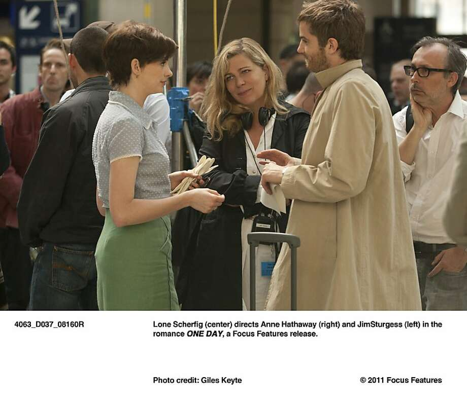 """Anne Hathaway, director Lone Scherfig and Jim Sturgess on the set of  """"One Day.""""  Scherfig (center) directs Anne Hathaway (right) and Jim Sturgess (left) in the romance ONE DAY, a Focus Features release. Photo: Giles Keyte, Focus Features"""