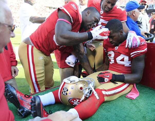 San Francisco 49ers wide receiver Josh Morgan, right, is tended to by teammate Vernon Davis, left, after being injured during the fourth quarter of their NFL football game against the Tampa Bay Buccaneers in San Francisco, Sunday, Oct. 9, 2011. San Francisco won 48-3. Morgan finished with five catches for 75 yards. (AP Photo/Paul Sakuma) Photo: Paul Sakuma, AP
