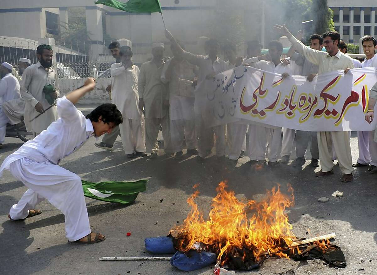 """A Pakistani protester beats a burning effigy of U. S. Adm. Mike Mullen, during an anti-American rally in Peshawar, Pakistan, on Tuesday, Oct, 4, 2011. U.S. pressure on Pakistan to attack Afghan militants on its soil will not succeed, the Pakistani prime minister told a gathering of political and military leaders. Banner reads """"Down with America rally."""" (AP Photo/Mohammad Sajjad)"""