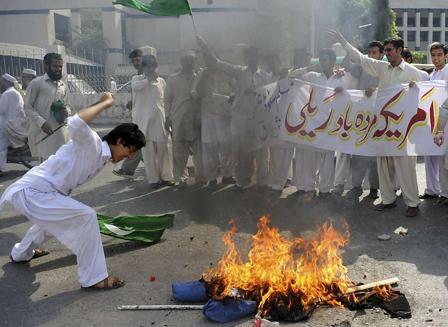 "A Pakistani protester beats a burning effigy of U. S. Adm. Mike Mullen, during an anti-American rally in Peshawar, Pakistan, on Tuesday, Oct, 4, 2011.  U.S. pressure on Pakistan to attack Afghan militants on its soil will not succeed, the Pakistani prime minister told a gathering of political and military leaders. Banner reads ""Down with America rally."" (AP Photo/Mohammad Sajjad) Photo: Mohammad Sajjad, AP"