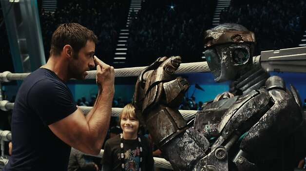"Charlie Kenton (Hugh Jackman, left) gives instructions to Atom while his son, Max (Dakota Goyo) looks on in DreamWorks Pictures' action drama ""Real Steel"". Photo: DreamWorks"