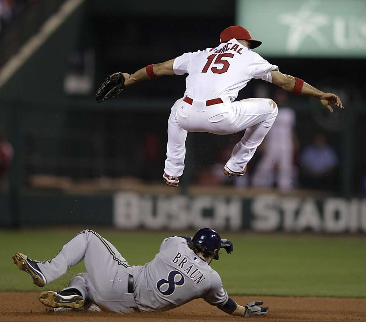 St. Louis Cardinals' Rafael Furcal (15) leaps over Milwaukee Brewers' Ryan Braun (8) to urn a double play on a ball hit by Prince Fielder during the third inning of Game 3 of baseball's National League championship series Wednesday, Oct. 12, 2011, in St. Louis. (AP Photo/Matt Slocum)
