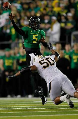 EUGENE, OR - OCTOBER 06:  Darron Thomas #5 of the Oregon Ducks is forced throws an interception as he is pressured by Aaron Tipoti #50 of the California Golden Bears on October 6, 2011 at the Autzen Stadium in Eugene, Oregon.  (Photo by Jonathan Ferrey/Getty Images) Photo: Jonathan Ferrey, Getty Images
