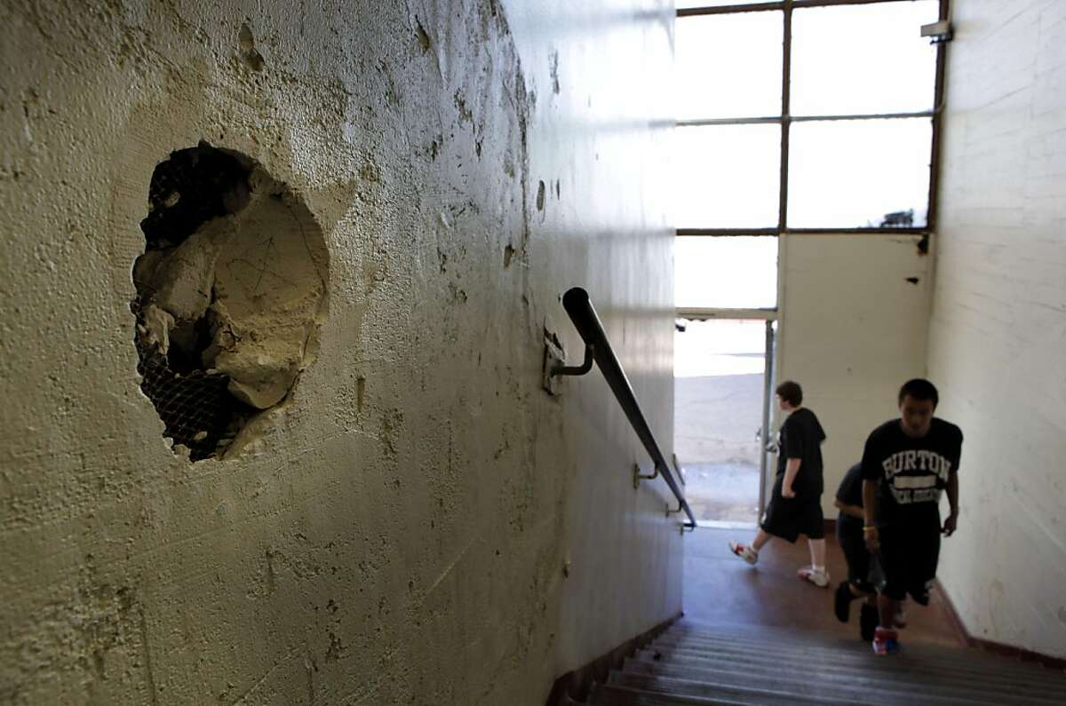 Student p[ass by the damaged walls of the gymnasium, on Friday October 7, 2011, one of the many areas of needed repair at Phillip and Sala Burton Academic High School in San Francisco, Ca. Money would become available if Proposition A were passed in the upcoming elections, funding that would fix the school.
