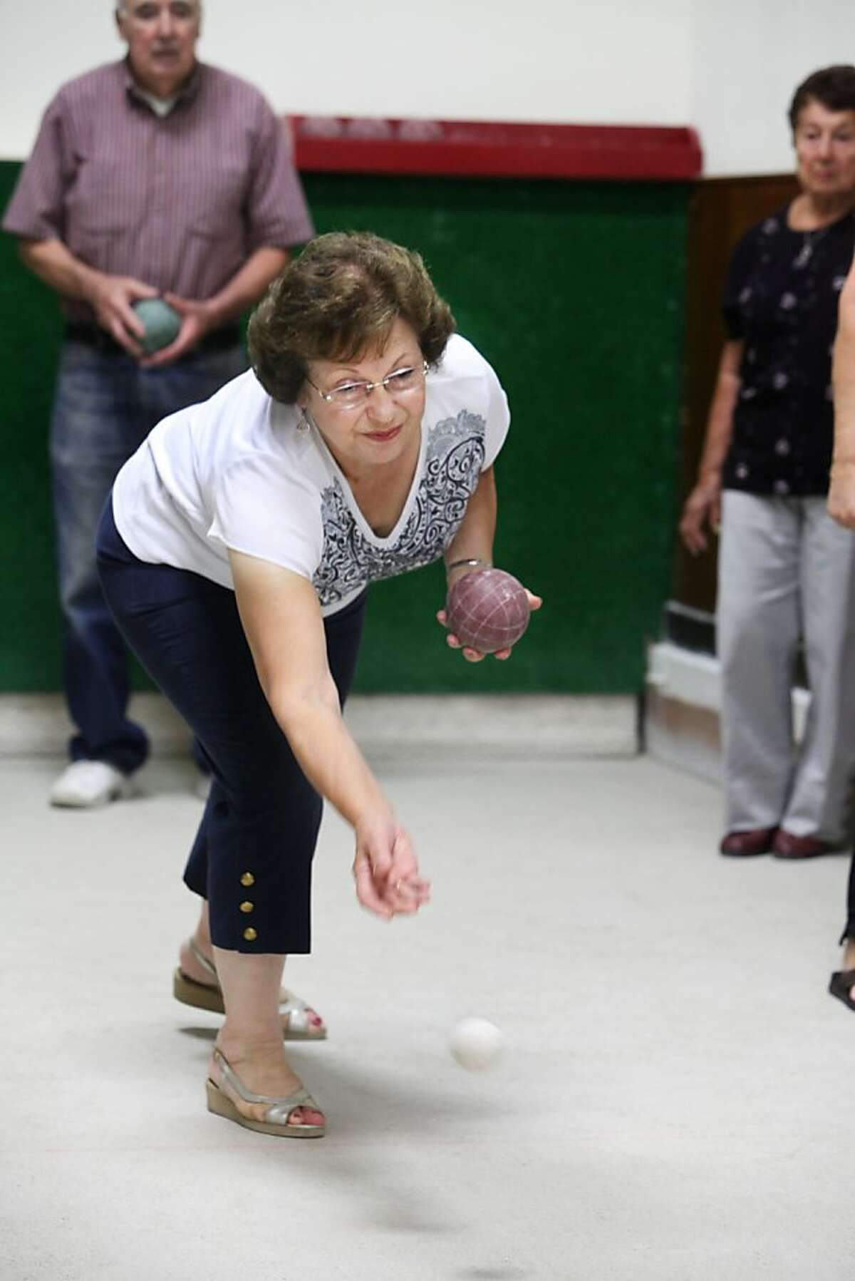 """Maria Pia Moro tosses the smaller """"jack"""" before the start of bocce at the Peninsula Italian American Social Club in San Mateo, CALIF on Sept. 27, 2011."""