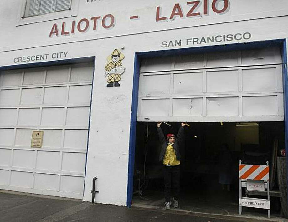 Annette Traverso opens a roll-up door for one of the last times at her family's Alioto-Lazio Fish Company in San Francisco, Calif., on Thursday, Jan. 13, 2011. The family has decided to shut down the business indefinitely until an extensive oil clean-up project by the Port and Exxon is completed directly behind their building. Photo: Paul Chinn, The Chronicle