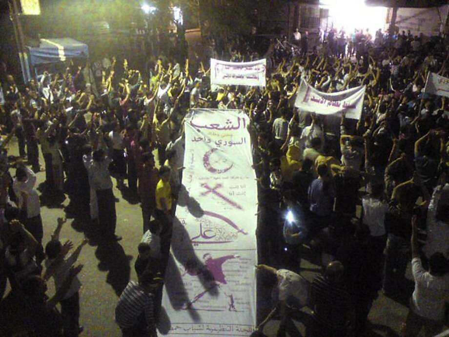 """In this citizen journalism image made on a mobile phone and provided by The Union of Homs City Neighborhood, anti-Syrian President Bashar Assad protesters hold up a banner with the signs of the Muslim Crescent, Christian's Cross, and Alawite sect by the sword, and the name of Imam Ali, with Arabic words reading:""""The Syrian people is one,"""" to show the unity between the Syrian sects during a demonstration against the Syrian regime, in Homs province, Syria, late Monday Oct. 3, 2011. Syrian troops going house to house have detained more than 3,000 people in the past three days in a rebellious town that government forces recently retook in some of the worst fighting since the country's uprising began six months ago, an activist said Monday. The formation of the new Syrian National council announced in Istanbul on Sunday. The council appeared to be the most serious step yet to unify a deeply fragmented dissident movement, and many Syrians in the southern and central regions of the country took to the streets in celebration, singing and dancing. (AP Photo/The Union of Homs City Neighborhood) EDITORIAL USE ONLY, NO SALES, THE ASSOCIATED PRESS IS UNABLE TO INDEPENDENTLY VERIFY THE AUTHENTICITY, CONTENT, LOCATION OR DATE OF THIS HANDOUT PHOTO   Ran on: 10-09-2011 A mobile phone image shows anti-Assad protesters holding a banner in Homs province late Monday with symbols representing Syrian sects and the words &quo;The Syrian people is one.&quo; Photo: AP"""