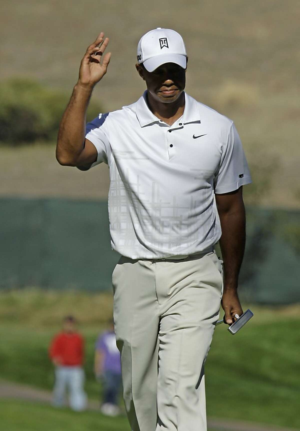 Tiger Woods waves to fans after making a birdie putt on the 11th hole during the third round of the Frys.com Open golf tournament Saturday, Oct. 8, 2011, in San Martin, Calif. (AP Photo/Ben Margot)