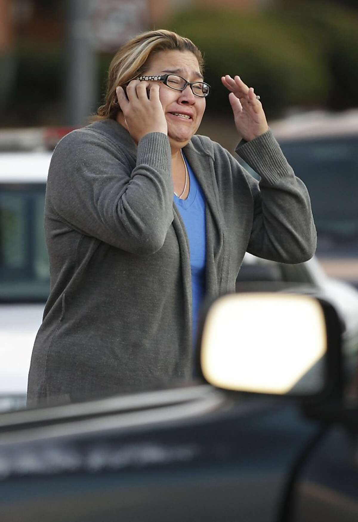 A woman who did not want to give her name reacts as she waits to hear about her father who works at the Lehigh Southwest Cement Company in Cupertino, Calif., Wednesday, Oct. 5, 2011. Authorities say a disgruntled employee opened fire at a meeting at the plant, killing two people and wounding six others. Santa Clara County Sheriff's spokesman Jose Cardoza said the shooting at Lehigh Southwest Cement Company occurred around 4 a.m. Wednesday. (AP Photo/Paul Sakuma)