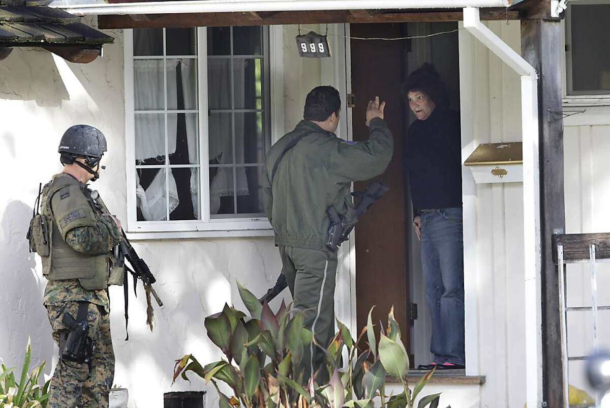 Police interview a resident in a neighborhood in Cupertino, Calif., Wednesday, Oct. 5, 2011 looking for a shooting suspect. Authorities say a disgruntled employee opened fire at the Permanente Quarry, killing two people and wounding at least six others during a morning meeting. Later Wednesday morning, a woman was shot in an attempted carjacking by a man matching the gunman's description, authorities said. (AP Photo/Paul Sakuma)