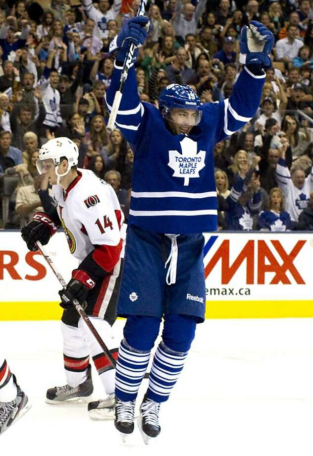Toronto Maple Leafs' Joffrey Lupul, right, celebrates scoring his team's third goal as Ottawa Senators' Colin Greening reacts during second period NHL hockey action in Toronto on Saturday  Oct. 8, 2011.  (AP Photo/The Canadian Press, Chris Young) Photo: Chris Young, AP