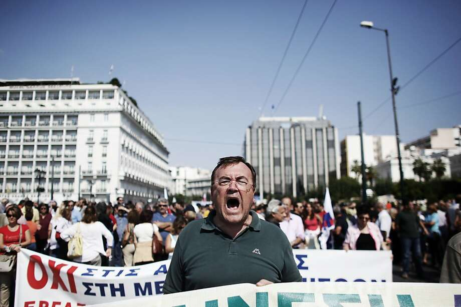 A demonstrator shouts slogans during a protest rally marking a 24-hour general strike, in Athens, on October 5, 2011. Greek police tear-gassed protestors in central Athens on Wednesday as public sector staff and students went on strike over austerity cuts, shutting down courts, schools and transport including flights. On Athens' central Syntagma Square outside the parliament building, police used tear gas to clear some of the 20,000 protestors, who included some 300 anarchists, after firebombs were thrown at them, an AFP reporter said. AFP PHOTO / Angelos TZORTZINIS (Photo credit should read ANGELOS TZORTZINIS/AFP/Getty Images) Photo: Angelos Tzortzinis, AFP/Getty Images